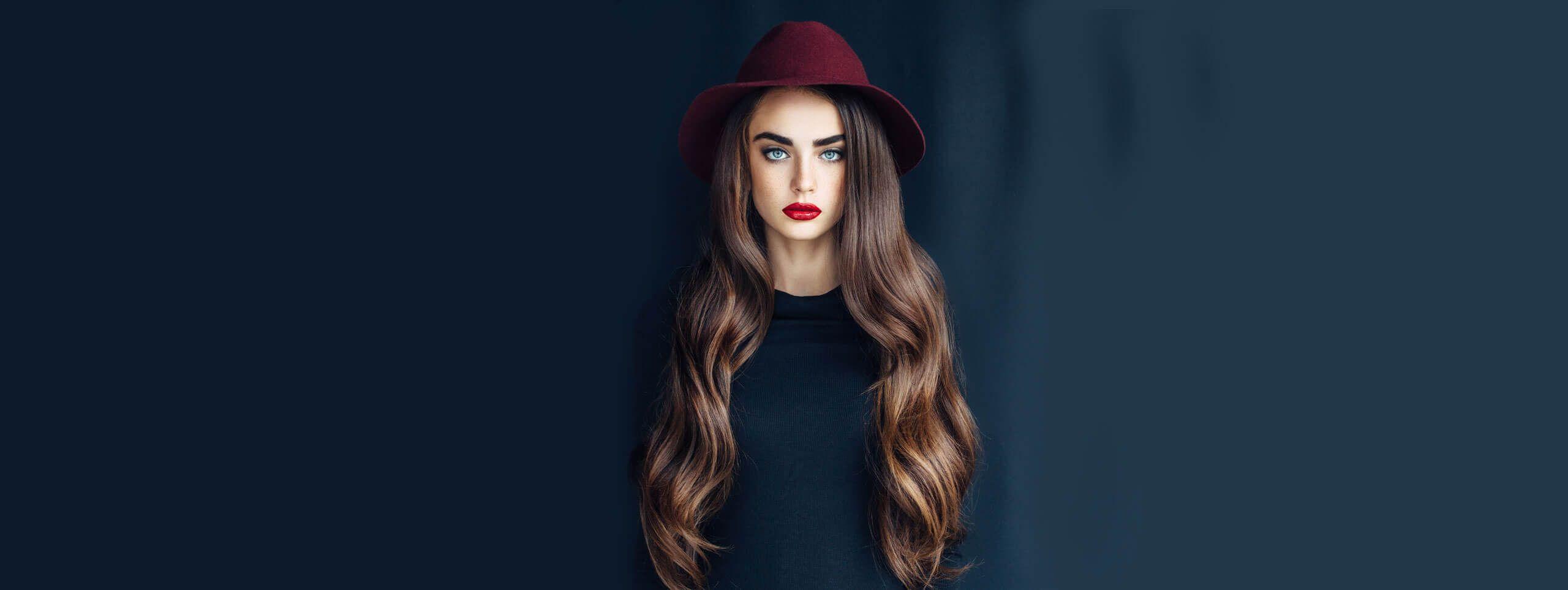 Kobieta z kapeluszem i długimi brązowymi włosami