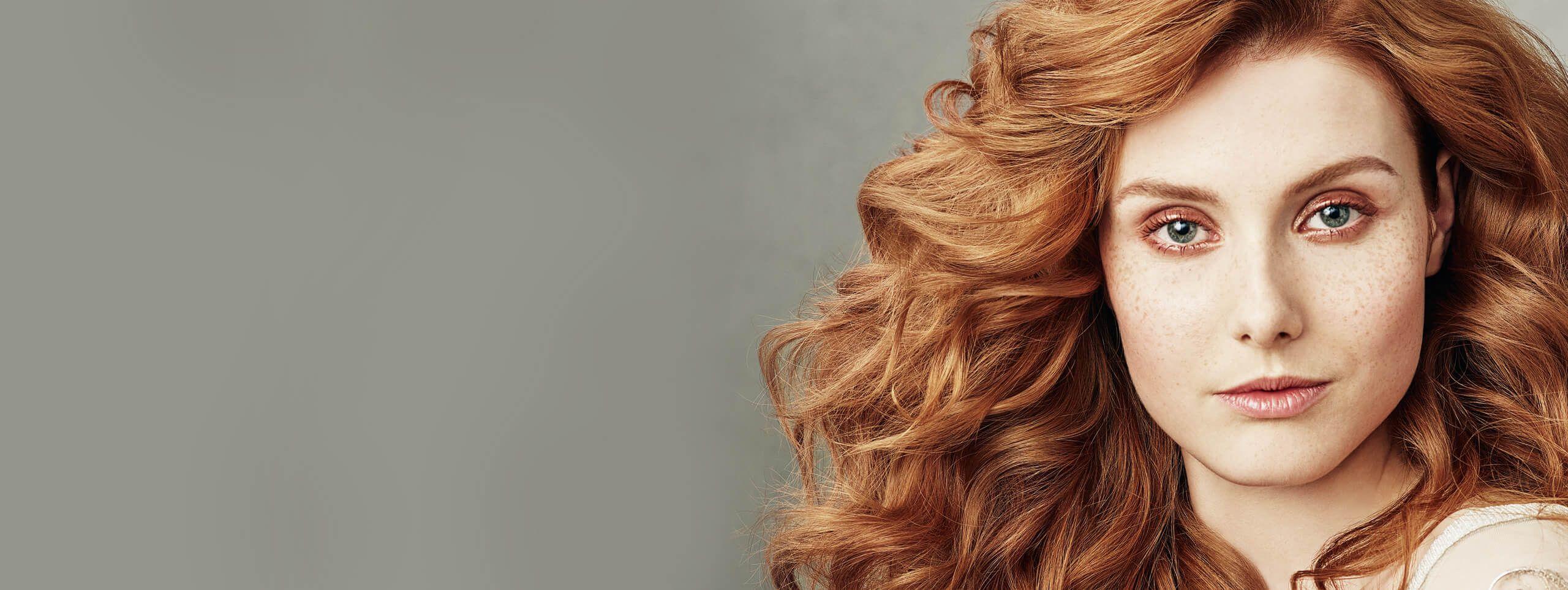 Kobieta z kręconymi rudymi włosami