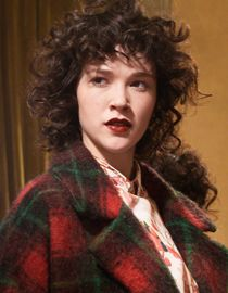 Brunette woman with short hair and corkscrew curls