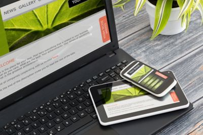 Photo of laptop, tablet and mobile phone with illustration of same web design on screen of all three devices
