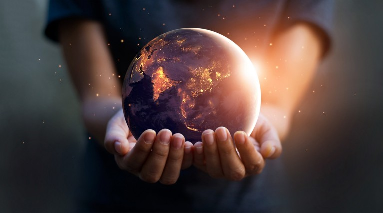 Two hands hold up a lit earth globe