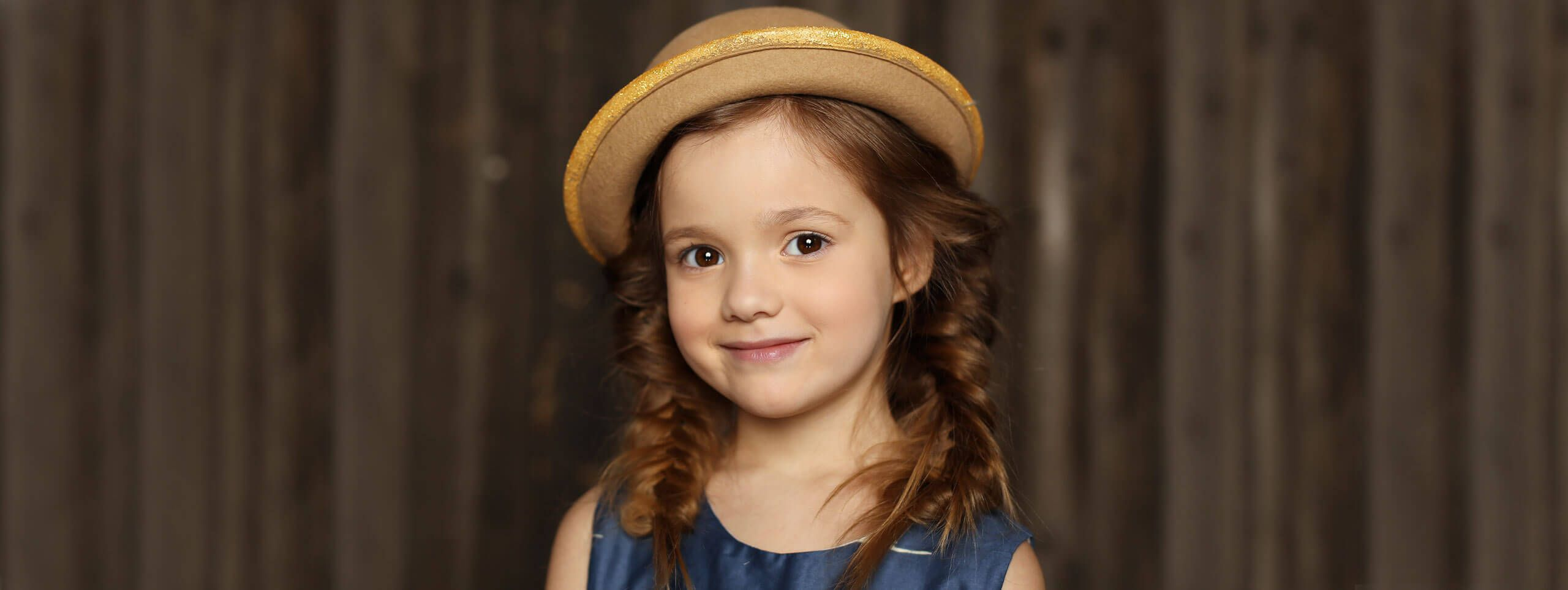 Little girl with curly hairstyle wearing a hat