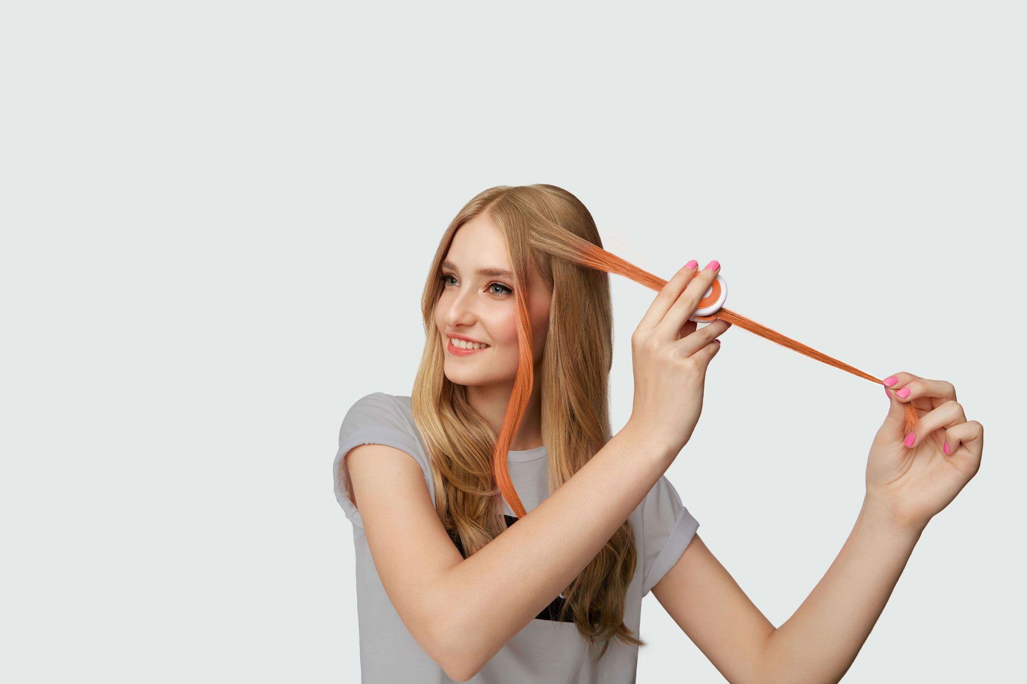 Djevojka plave kose nanosi kredu u boji narančaste boje