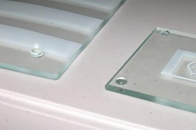 ¿Cómo pegar protecciones de caucho en un posavasos de cristal?