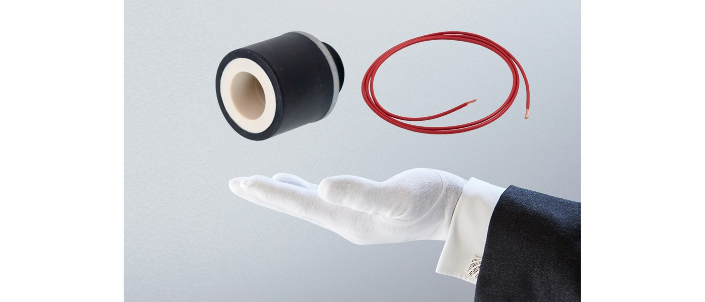 The hand of a butler underneath an electronic component and bit of red wire
