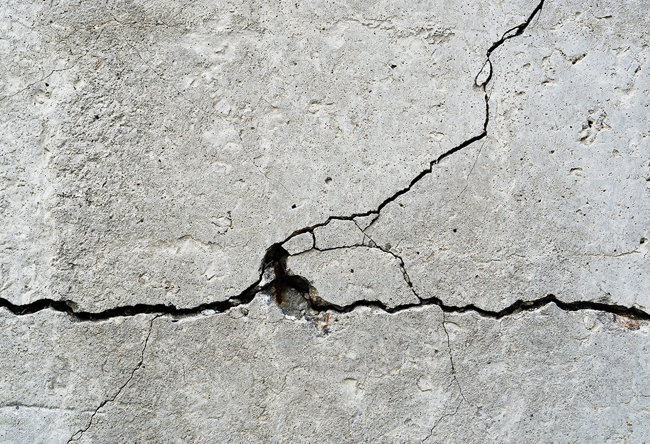 Thin cracks in a concrete wall.