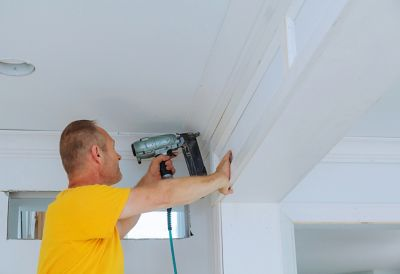 Man securing a crown molding in place