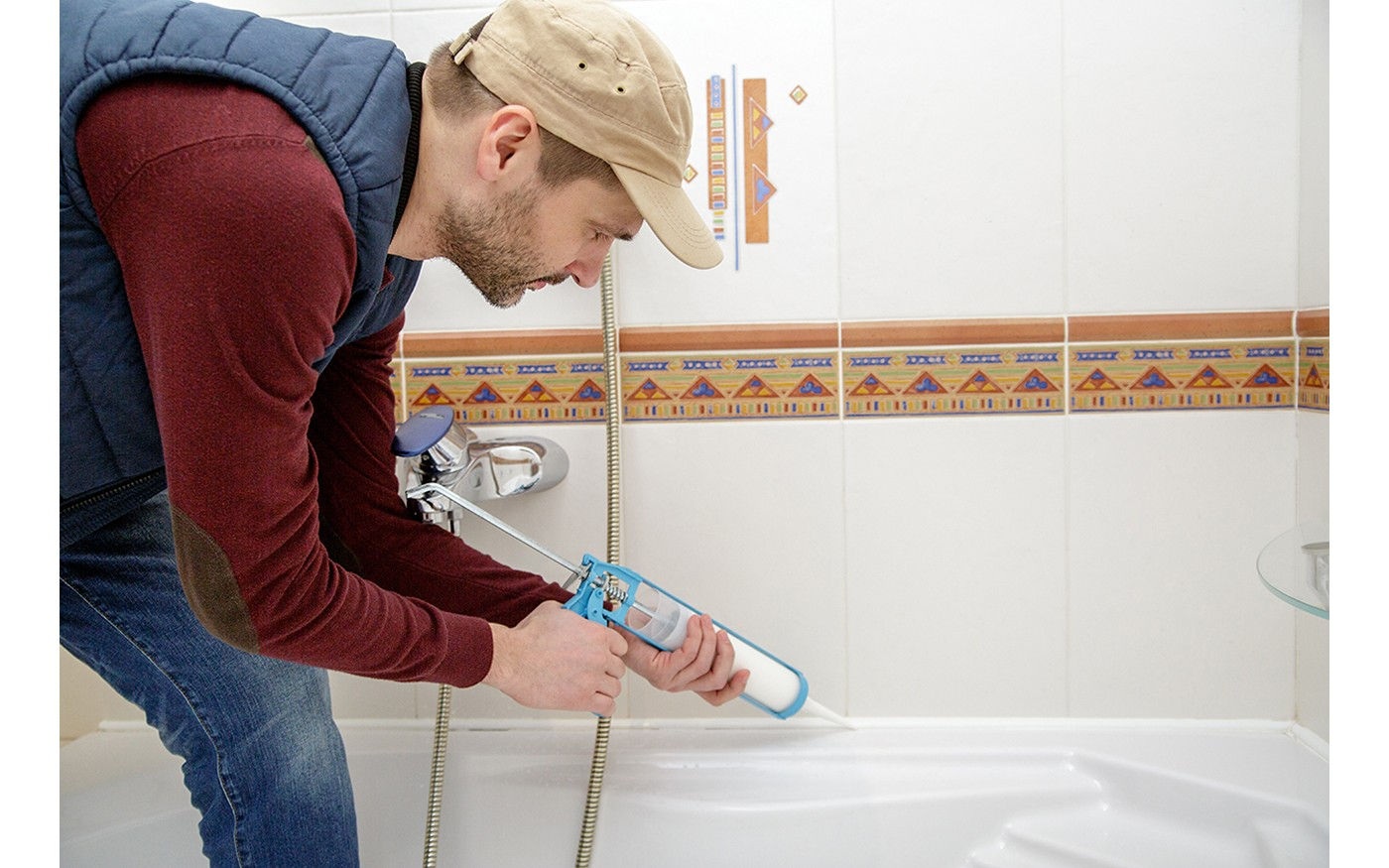 Caulking being applied to a white bathtub in a clean room