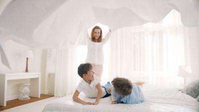 """Antrasis diskų """"Persil"""" privalumas - švytintis ryškumas - besišypsančios mamos su savo laimingais vaikais fone."""