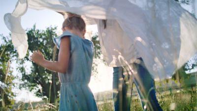 """Trečiasis diskų """"Persil"""" privalumas - ilgalaikė gaiva - merginos, bandančios rasti kelią tarp besiplaikstančių džiūstančių skalbinių, fone."""