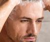 Mann steht unter der Dusche und shampooniert seine Haare