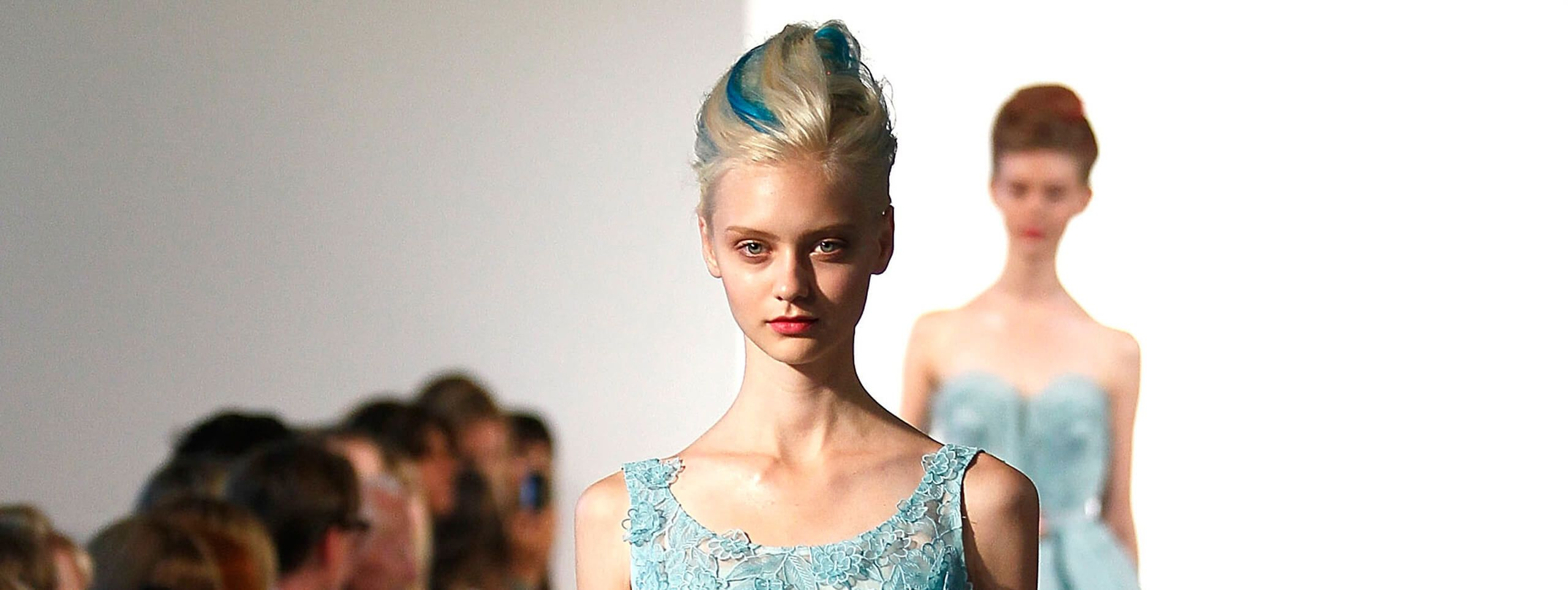 Model accentuates blonde updo hairstyle with blue streaks