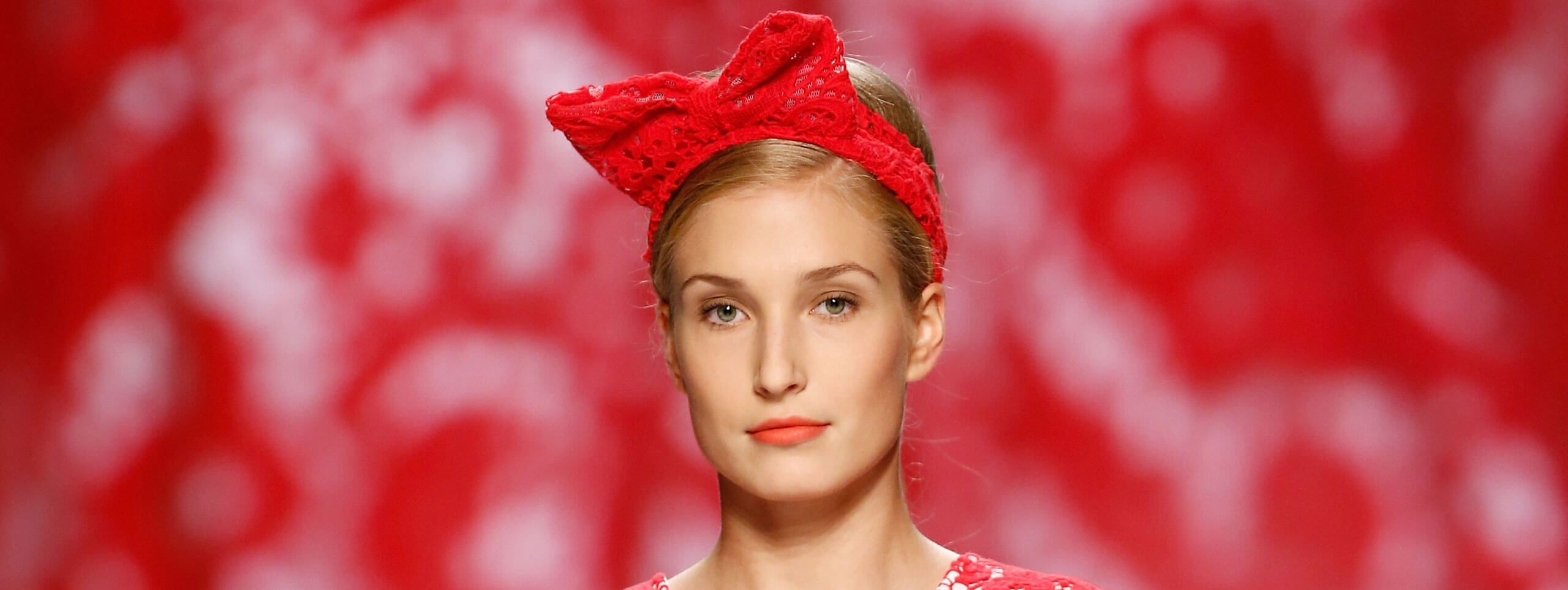 Model completes updo hairstyle with red bow headband