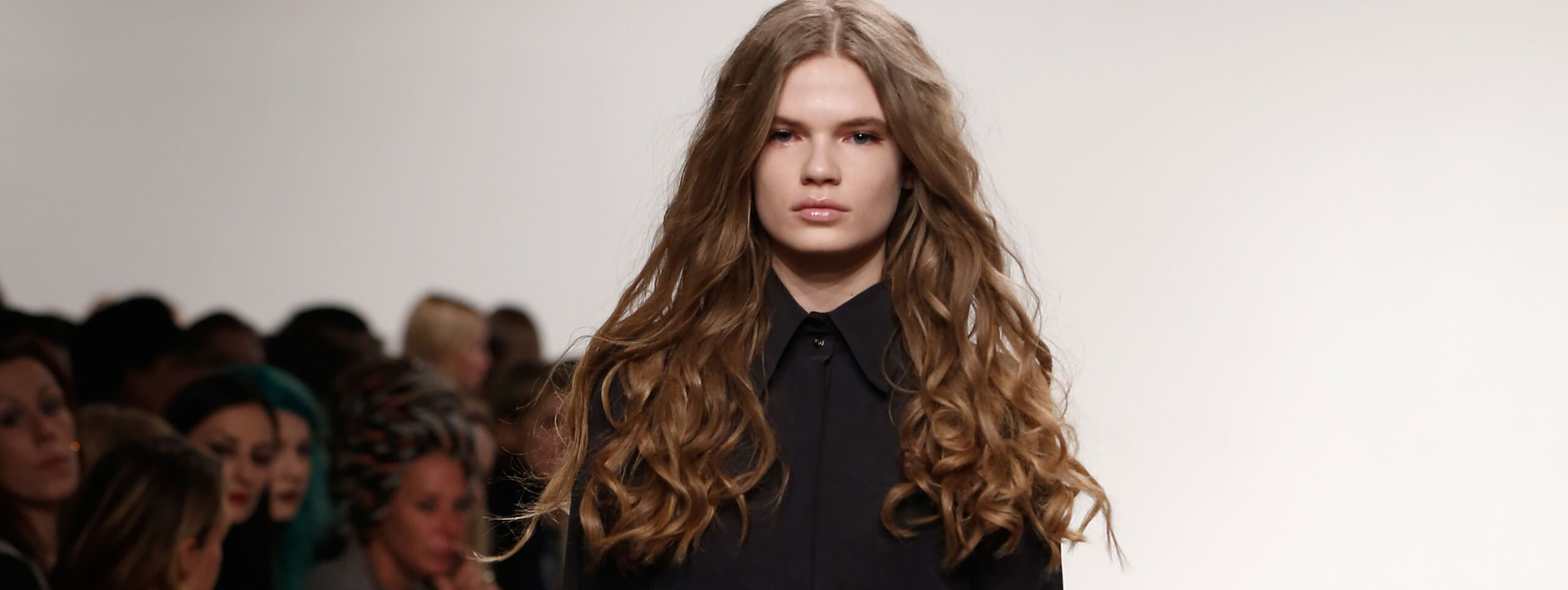 Model wears curly hairstyle with straight roots