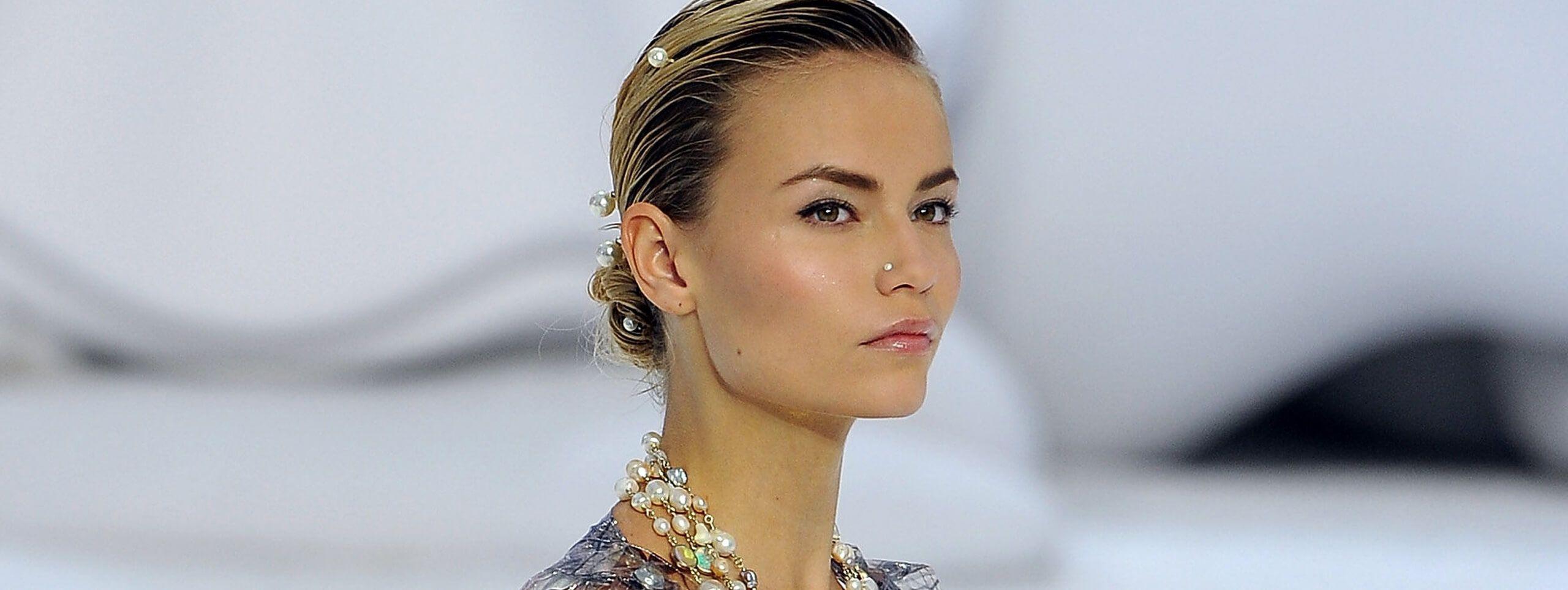 Model wears hair in a low bun, an elegant festive hairstyle