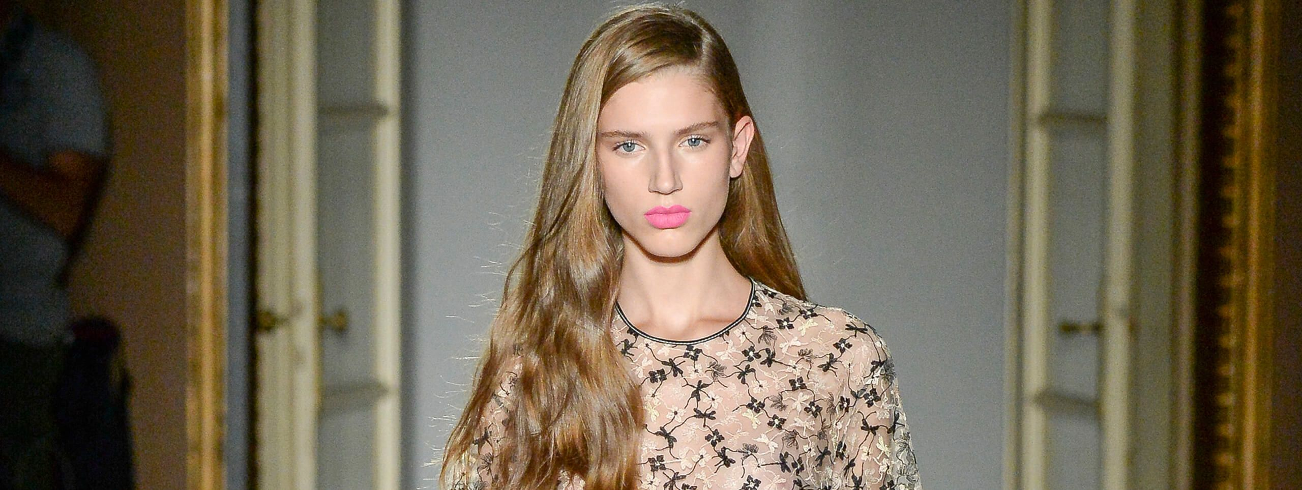 Model wears long brown hair in sideparting hairstyle