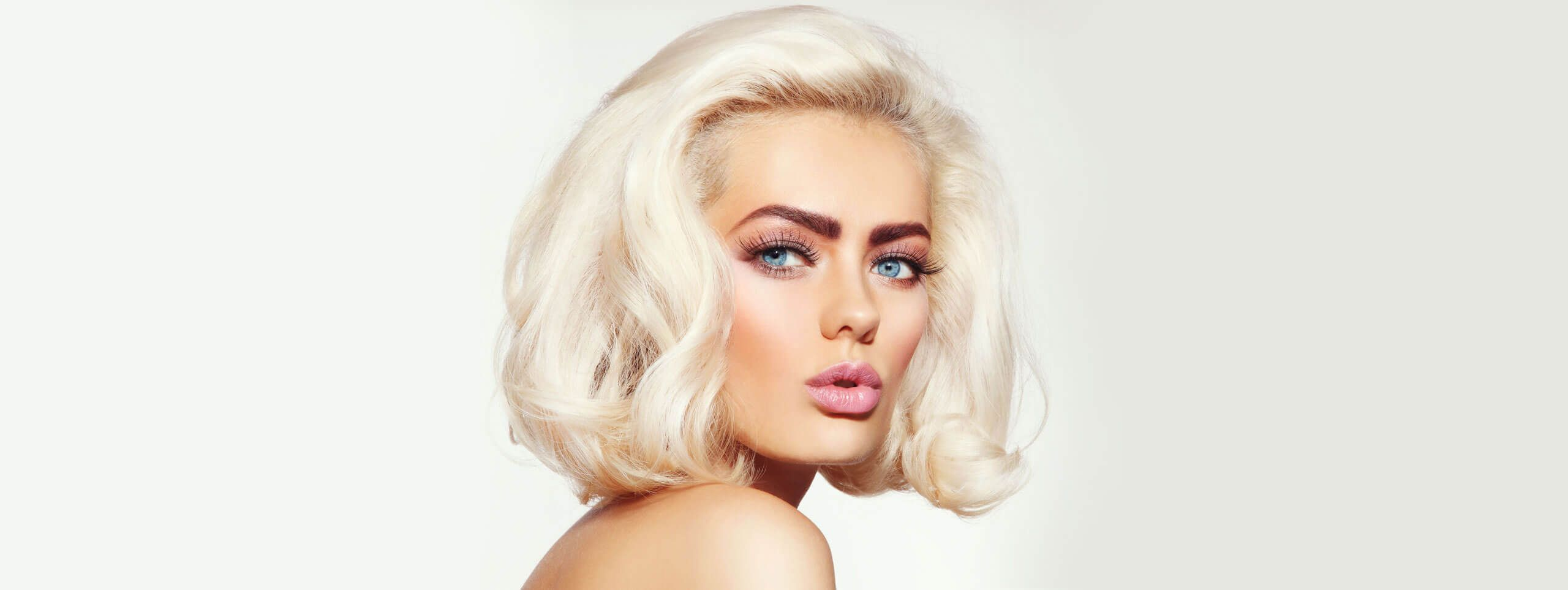 Model wears makeup to complement platinum blonde hair color