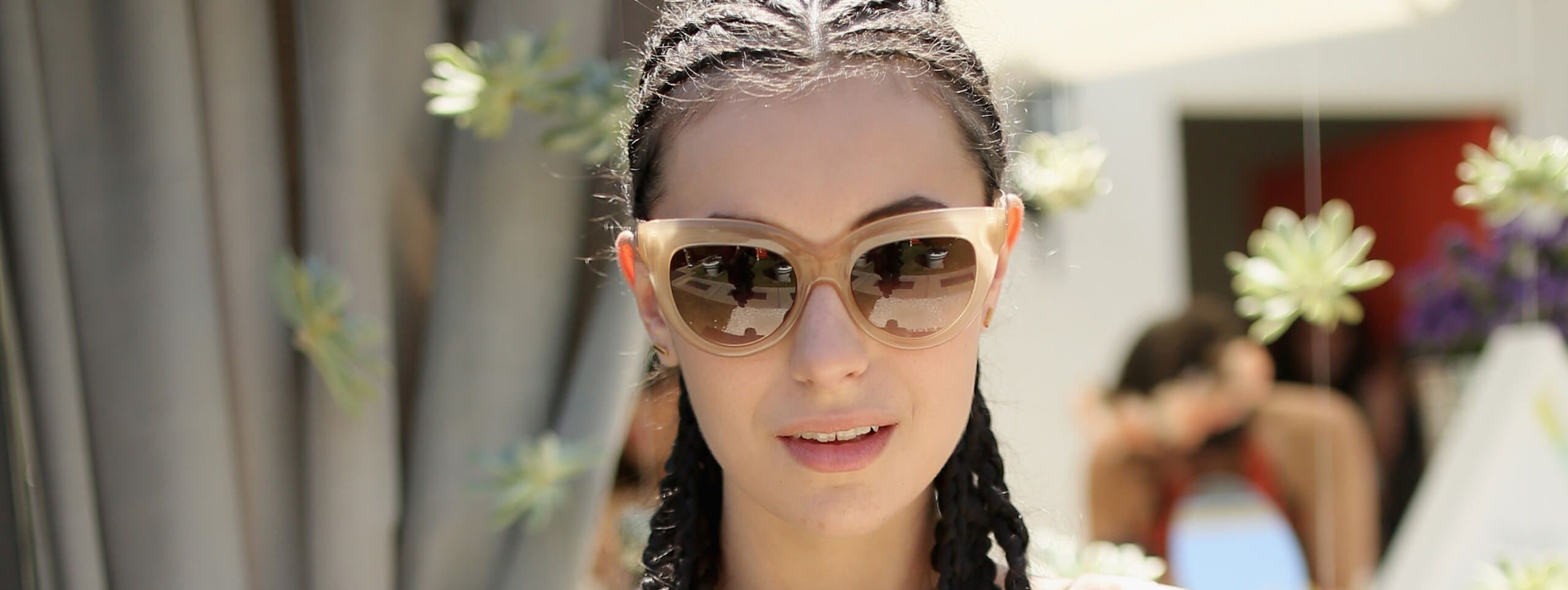 Model with braided hairstyle and sunglasses