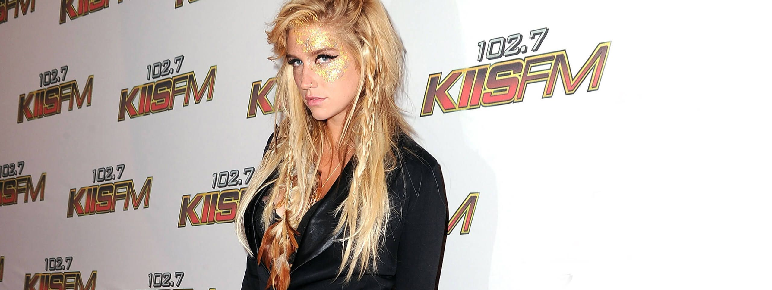 Model with glitter on her face and feathered hairstyle