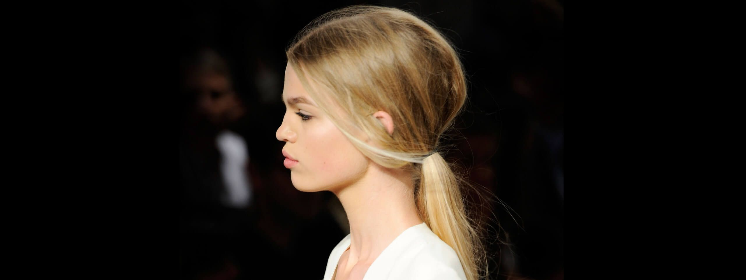 Model with hairstyle tied into a loose pony