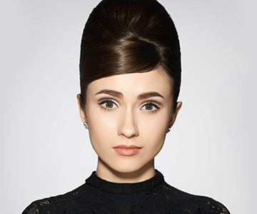 Woman wears a beehive hairstyle