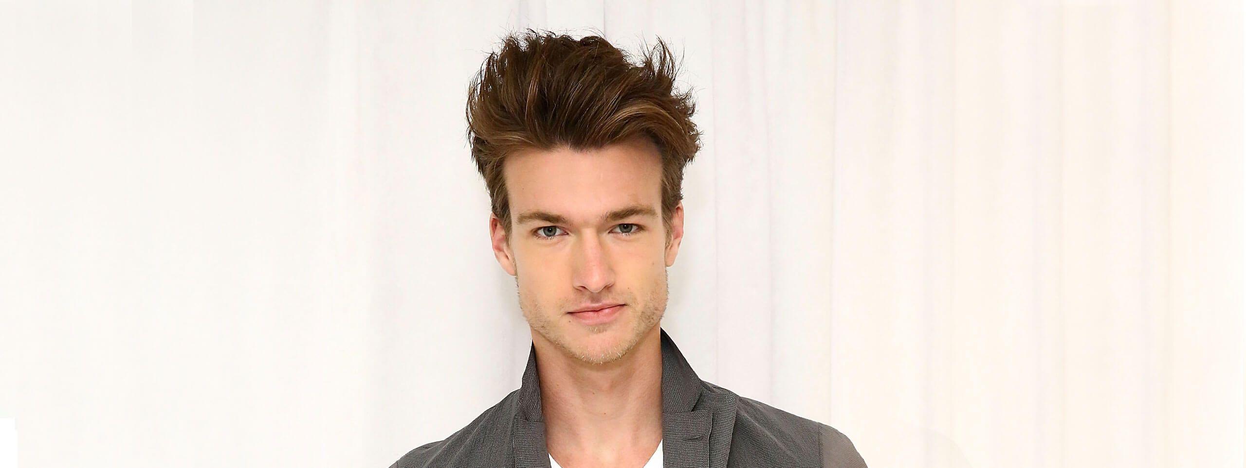 Model z modnie uniesionymi brązowymi włosami na czubku głowy