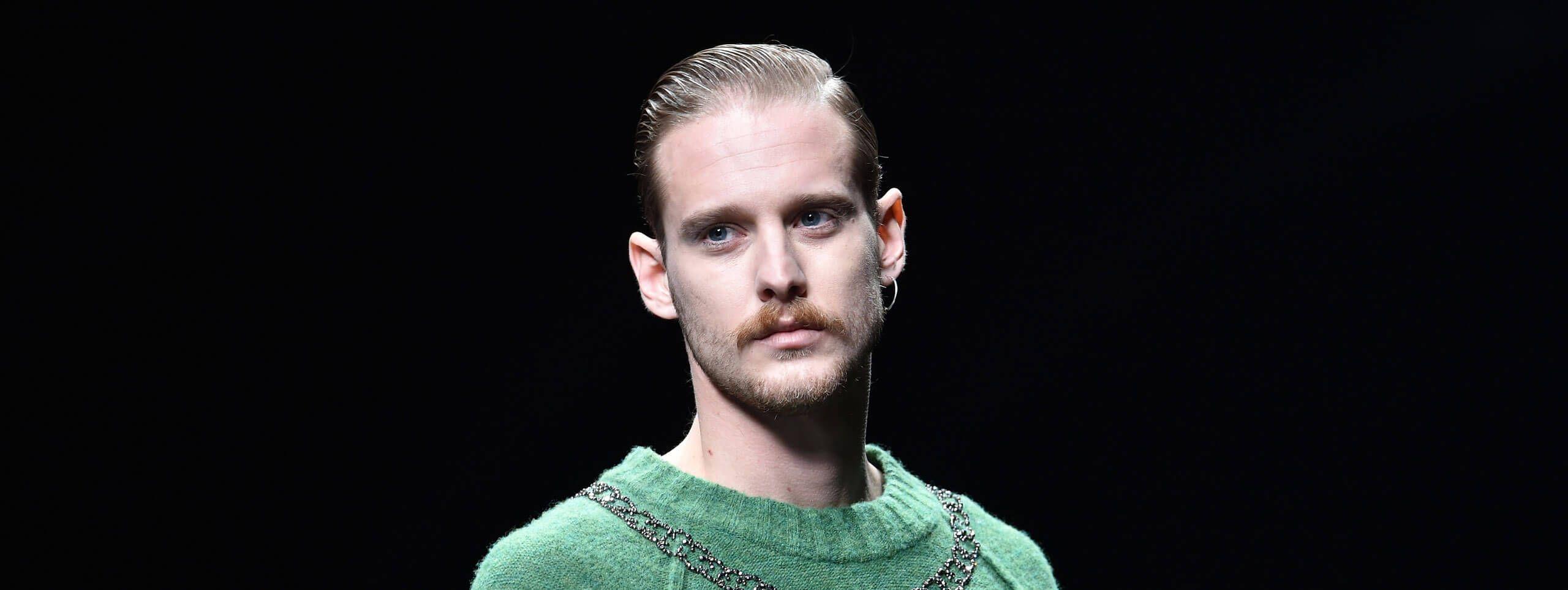 Model z wąsami i włosami zaczesanymi na żel
