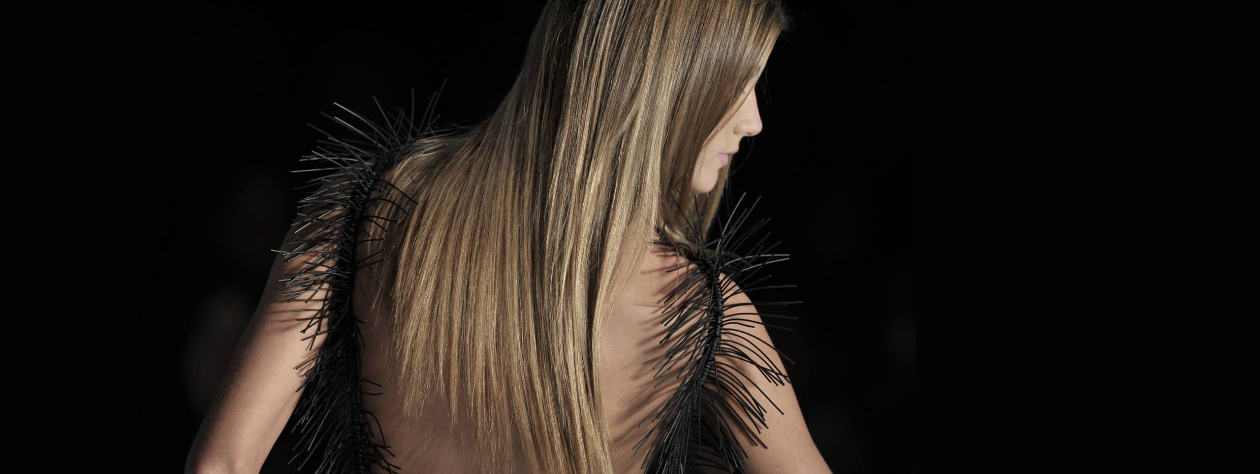 Modelka z długimi rozpuszczonymi włosami stojąca tyłem