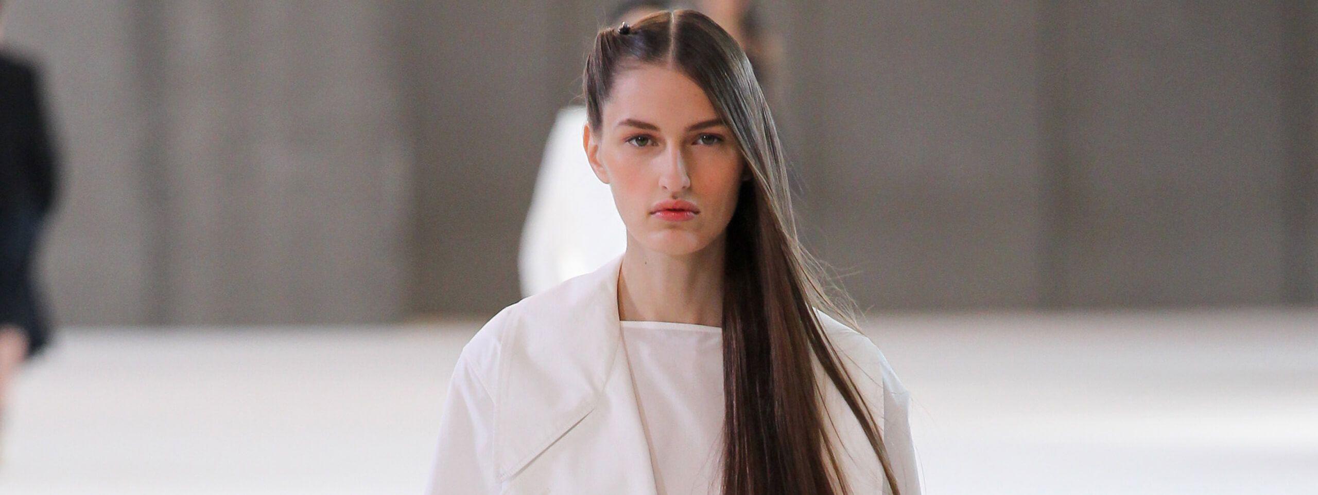 Modella con capelli lisci castani raccolti da un lato
