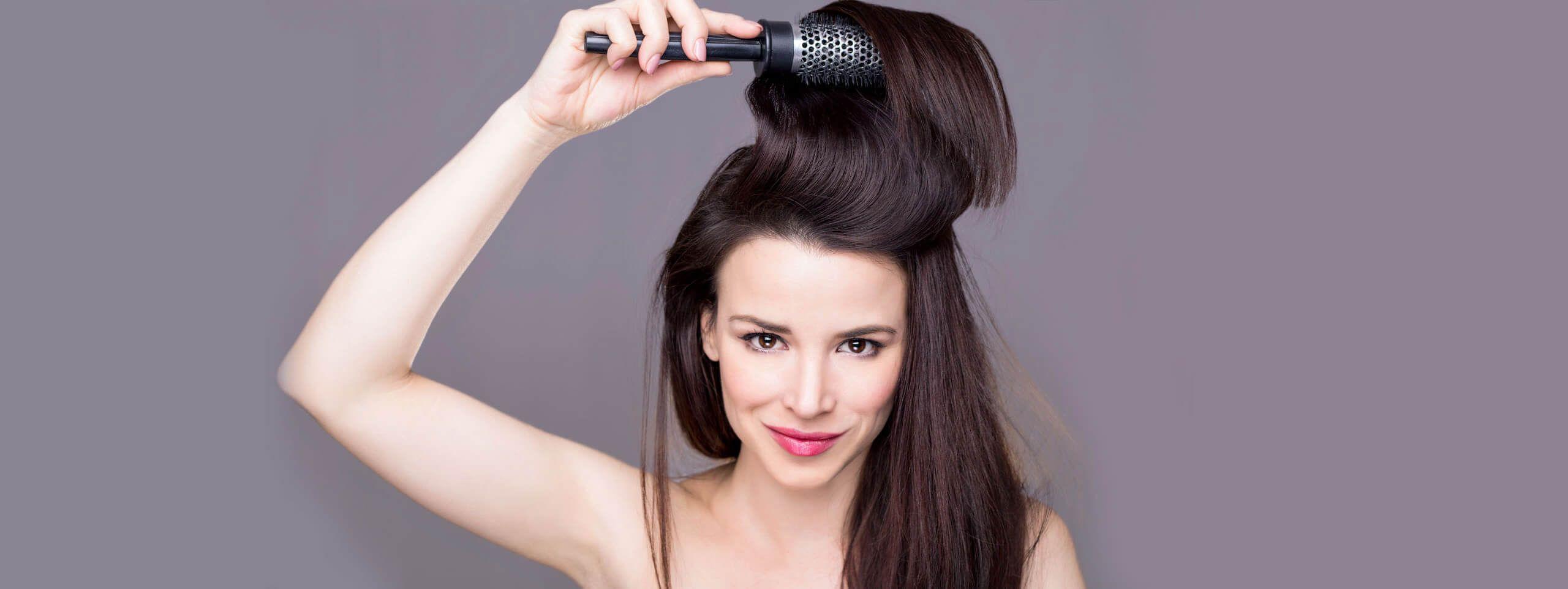 Modelo peinándose hacia atrás pelo castaño volumen