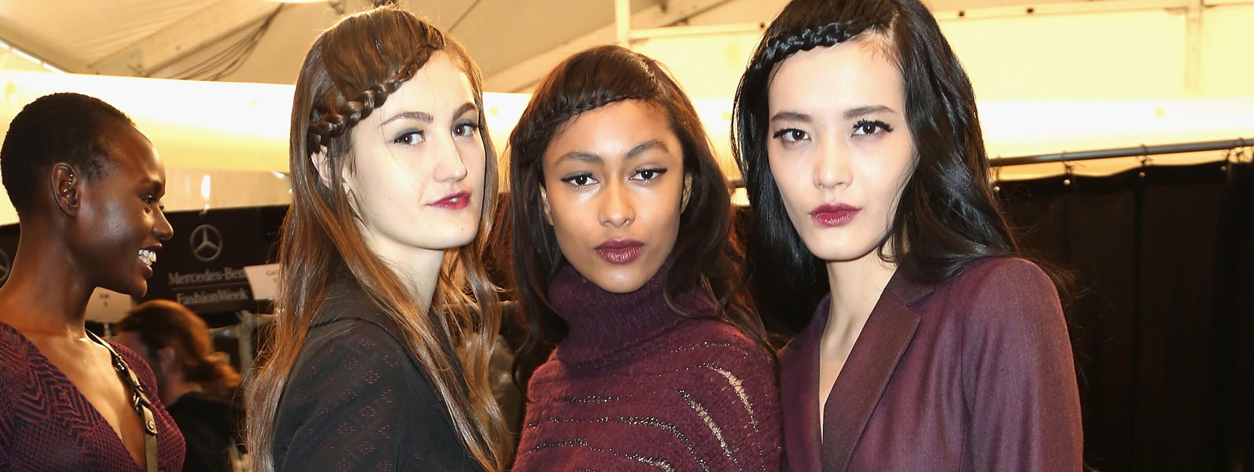 Models wear mid-length dark hair in braided hairstyle