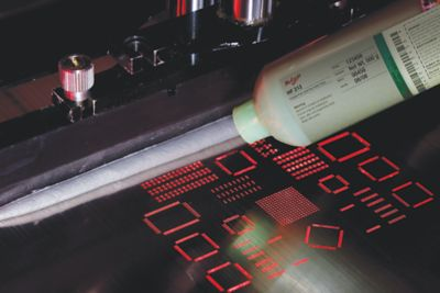 Photo of packaging with label  of mulicore hf212 solder paste being dispensed onto stencil