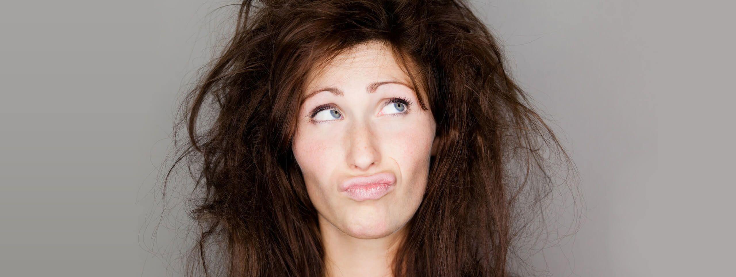 Niezadowolona kobieta z suchymi potarganymi włosami
