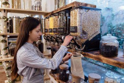 No Waste, Frau in Supermarkt, der unverpackte Lebensmittel anbietet
