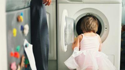 Rückenansicht eines kleines Mädchens im rosa Tütü, die tief in die Waschtrommel schaut.