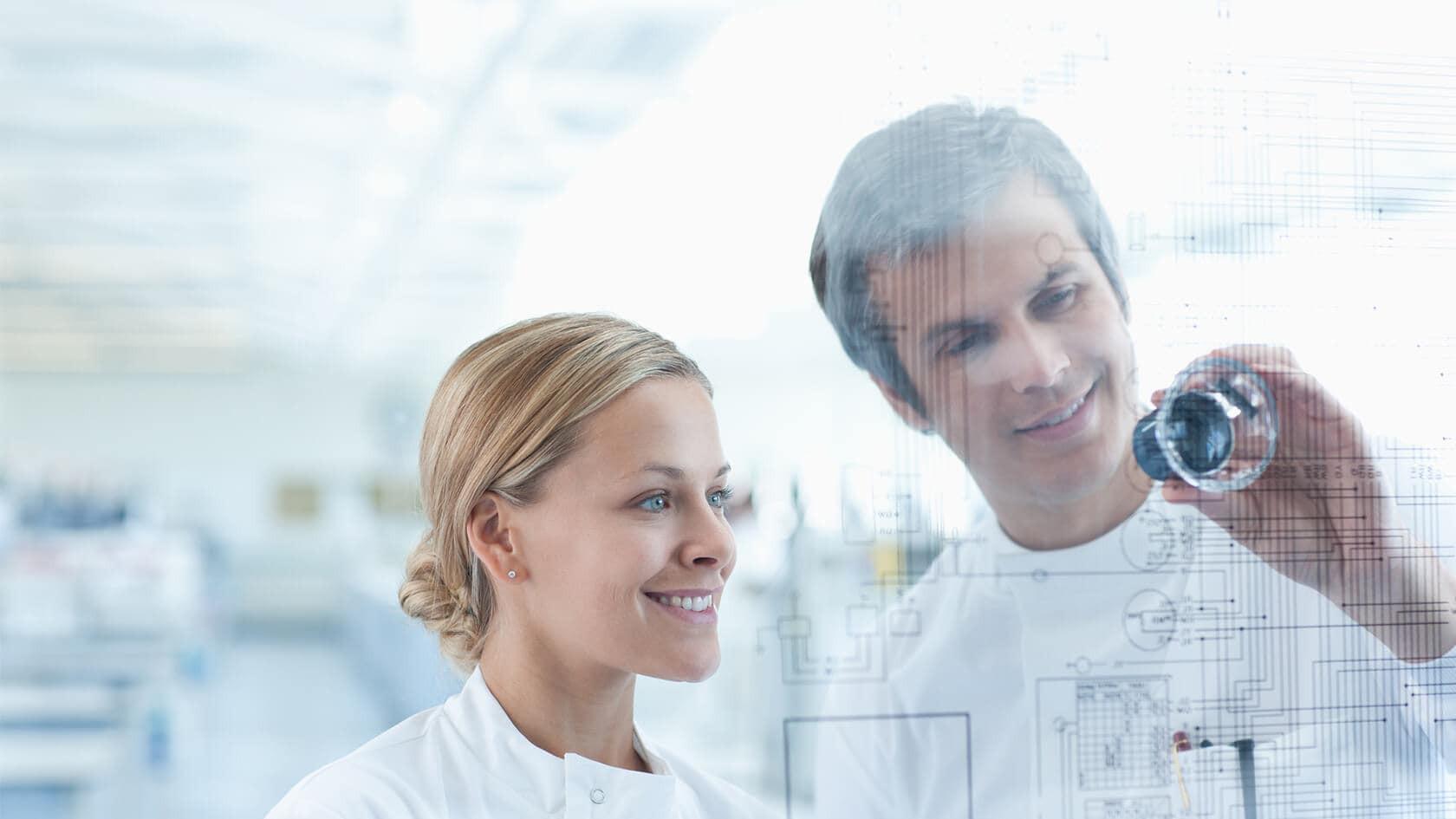 Eine Frau und ein Mann in Laborkleidung schauen sich gemeinsam eine Zeichnung auf Plexiglas an.