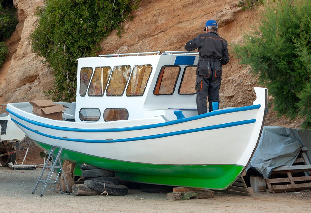 Ein Mann repariert ein Holzboot mit Epoxidkleber