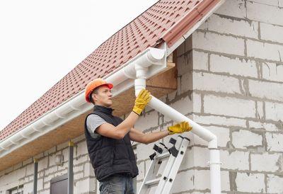 Mann montiert Dachrinne