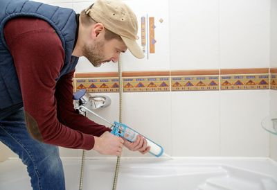 Mann/Frau dichtet eine Badewanne mit Silikon ab