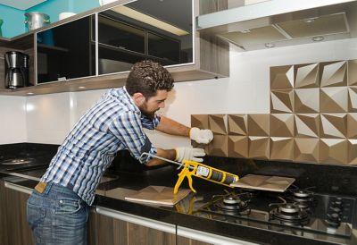 Mann/Frau bringt Küchenrückwand an