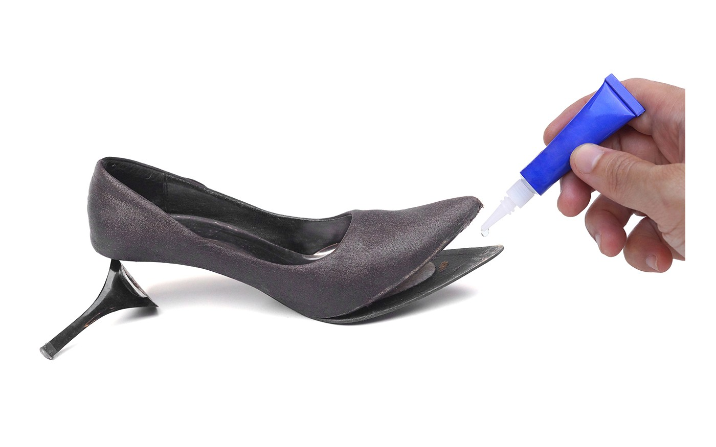 Eine abgenutzte Schuhsohle, die mit Schuhkleber repariert wird