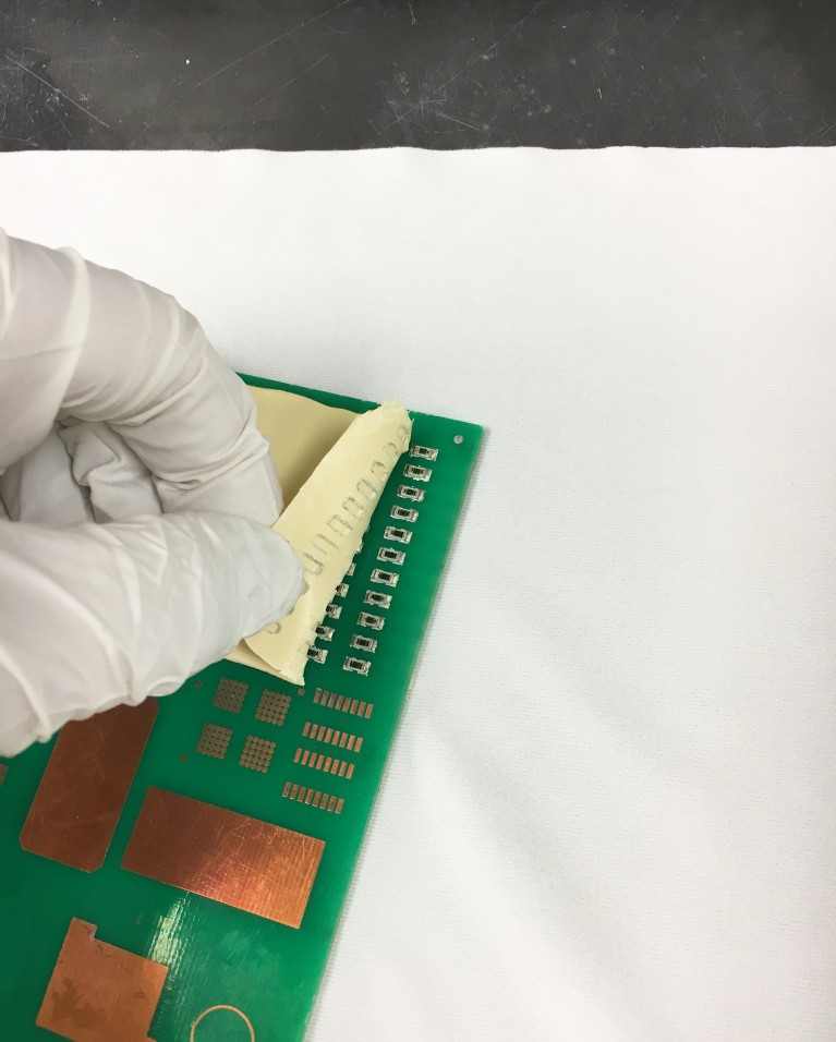 Photo of gloved hand peeling back bergquist peelable thermal interface material from printed circuit board this unique liquid gap filler material offers post-assembly reworkability