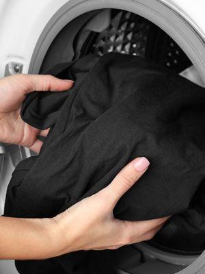 Schwarze wäsche wird in waschmaschine gelegt