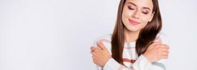 Eine junge Frau streicht sich mit geschlossenen Augen über die Oberarme.