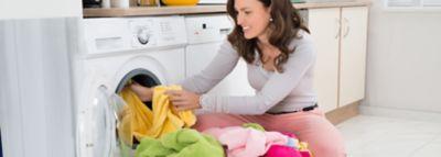 Eine Frau belädt eine Waschmaschine mit bunten Handtüchern.