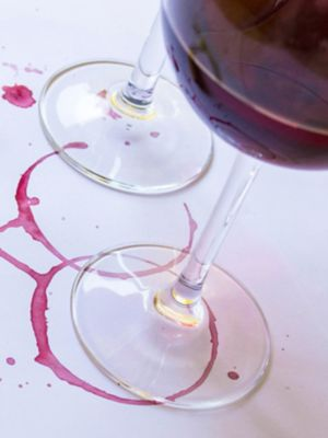 A glass of red wine spilled onto a button-up shirt.
