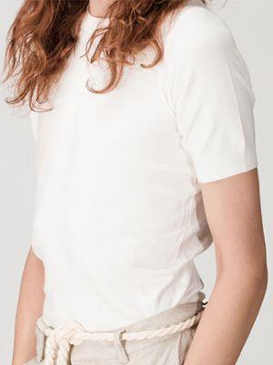 Oberkörper-Ansicht einer Frau in einem hellen Shirt.