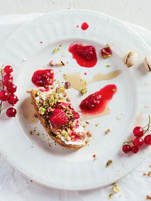 Ein Teller mit Essensresten: Belegtes Crostini mit Pistazien, Beeren und Saft von Beeren drumherum.
