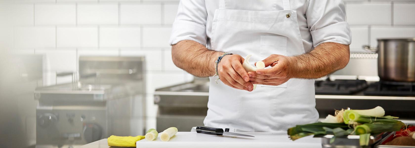 Ein Koch in Arbeitskleidung bei der Arbeit.