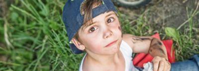 Junge mit blauer Basecap und weißem Unterhemd wischt sich die Hände sauber